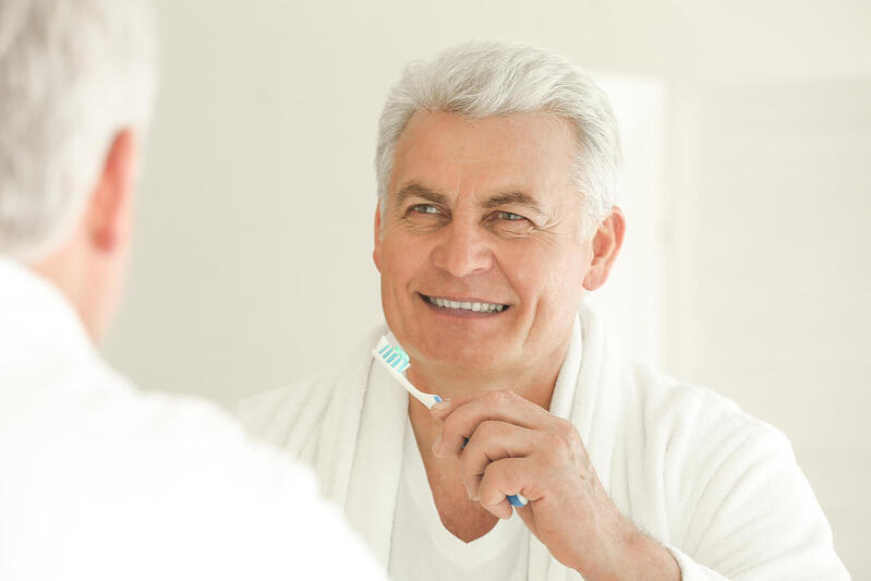 bigstock-Senior-man-cleaning-teeth-at-h-186700081